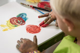Little boy having fun painting with fingers - 220669822