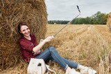 young girl makes selfie on smartphone on the background of haystack - 220671033