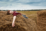 young girl having fun in the field, lying on a haystack - 220671059