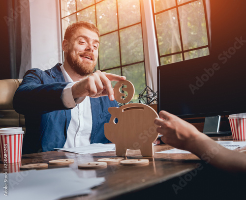 Leinwanddruck Bild Businessman holds a coin near wooden piggy. Money box. Collecting money with earning bank.