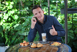 A young guy speaks on the phone in a summer cafe. Morning coffee and pastries for breakfast. The concept of a business morning. - 220687286