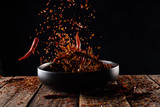 Pouring cayenne pepper powder into the bowl on wood table,Motion blur - 220691053