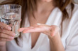 Leinwandbild Motiv Woman holding pill and glass of water in hands taking emergency medicine, supplements or antibiotic antidepressant painkiller medication to relieve pain, meds side effects concept, close up view