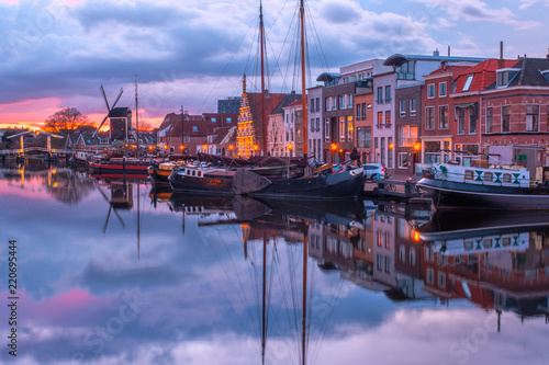 View of the canals of the city of Leiden with hoses, ships and boats at sunset. View of city channel with ships, the city of Leiden, Netherlands.