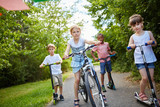Group of kids riding bike and scooter