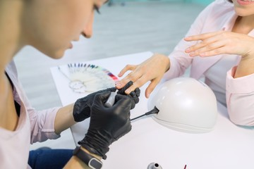 Young beautician in beauty nail salon doing manicure, paints nails. Nail and hand care in beauty salon.