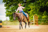 Cowgirl doing horse riding on countryside meadow - 220706802
