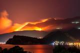 Wild fire blazing on hills above sea town. - 220709282