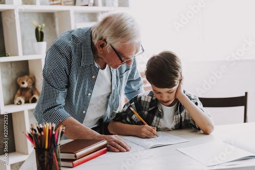 Leinwandbild Motiv Grandson Doing School Homework with Old Man Home