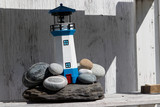 Macro of lighthouse and rocks on wooden shelf, nobody, bright white and blue - 220730297