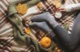 Women's hands and feet in sweater and woolen cozy gray socks holding cup of hot coffee with marshmallow, sitting on plaid with pumpkin, knitted scarf, leaves. Concept winter comfort, morning drinking. - 220737626