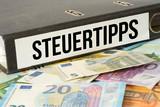 Ein Ordner mit dem Aufdruck Steuertipps und Euro Geldscheine