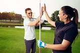 Happy golf player couple giving high five while standing on field - 220747434