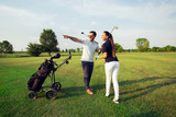 Young sportive couple playing golf on a golf course - 220747485