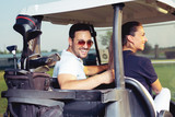 Couple smiling and driving in buggy in golf course - 220747628