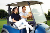 Couple smiling and driving in buggy in golf course - 220747687