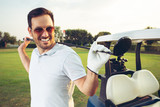 Closeup portrait of man smiling while holding golf club - 220747802