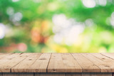 Empty wooden table top and green bokeh display montage for product with space. - 220747819