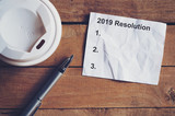 Resolution for 2019 word on paper with pen and coffee cup on wooden table. Business concept. - 220749026