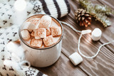 Hot cocoa with marshmallow in a white ceramic mug surrounded by winter things on a wooden table. The concept of cosy holidays and New Year. - 220751428