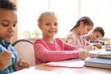 Cute children doing homework in classroom at school - 220752084