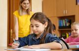 Cute girl doing homework in classroom at school - 220752086