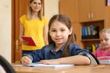 Cute girl doing homework in classroom at school - 220752088