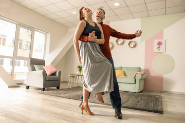 Happy mature couple dancing at home