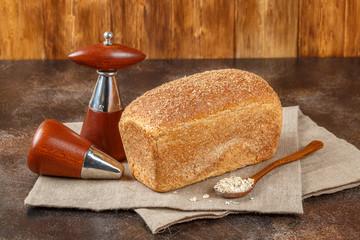 Loaf of fresh bread sliced on wooden background