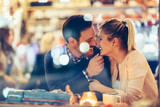 Romantic couple dating in pub at night - 220758610