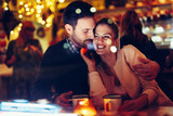 Romantic couple dating in pub at night - 220758640