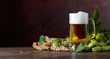 Mug of beer, grain and hops on a old wooden table. - 220759078