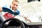 professionelle Autowäsche als Dienstleistung - Mann reinigt Autoscheibe - Sicherheit im Straßenverkehr durch saubere Frontscheibe im Auto - 220759023