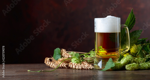 Sticker Mug of beer, grain and hops on a old wooden table.