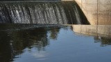 Water flowing over a dam of an old hydroelectric power station. - 220762067