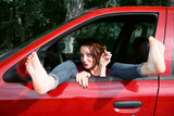 young woman driver resting in a red car, put her feet on the car window and flirting, happy travel concept - 220764497