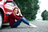 young girl sitting on the road by the red car - 220764641