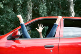 young woman driver resting in a red car, put her feet on the car window and gesturing, happy travel concept - 220764693