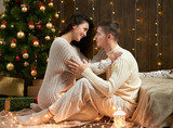Young couple sit on floor in dark wooden interior with lights. Romantic evening and love concept. New year holiday. Christmas lights and decoration. Dressed in white. - 220764806