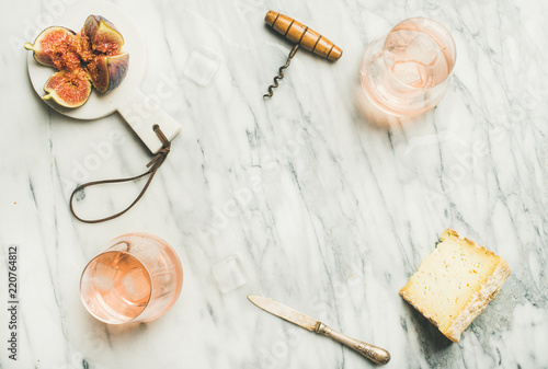 Leinwanddruck Bild Flat-lay of glass of rose wine with ice cubes, cheese and fresh figs over marble background. Summer wine and snack set, top view, copy space