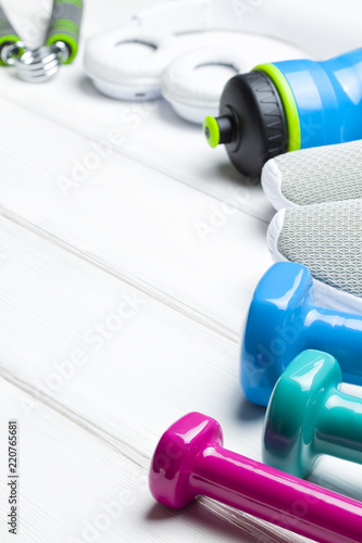 Wall mural Sport and fitness symbols - sneakers, water and dumbbell on wooden wall background