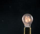 Burning old light bulb on black backround - 220767472