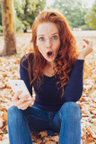 Shocked young redhead woman staring at the camera