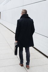 Rear view of man walking with briefcase