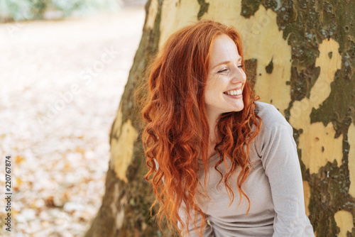 Smiling young woman leaning against a tree trunk