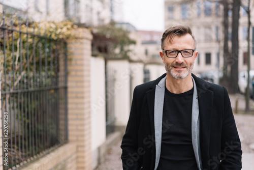 Leinwanddruck Bild Older stylish man walking on an urban sidewalk