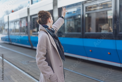 Poster Stylish woman waving at a passing tram