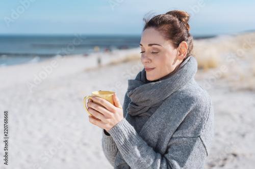 Leinwandbild Motiv Young woman enjoying a relaxing cup of coffee