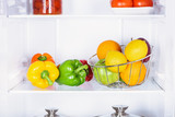 bell peppers, oranges and apples in fridge - 220777677