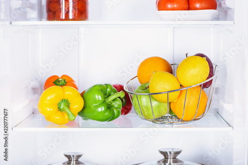 Plakat bell peppers, oranges and apples in fridge